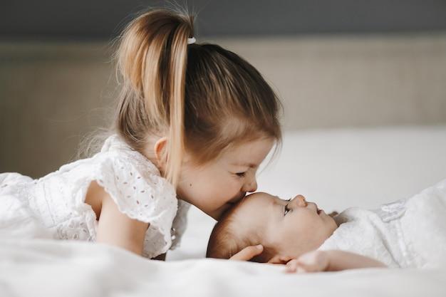 Die ältere schwester küsst ein kleines mädchen mit geschlossenen augen auf die stirn