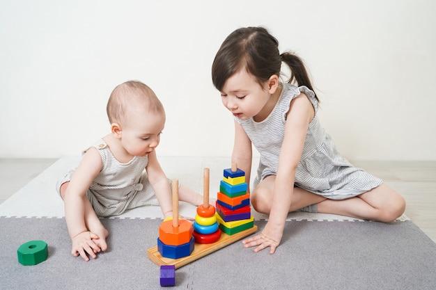 Die ältere schwester spielt mit der jüngeren. mädchen sammeln die pyramide. freundliche schwestern spielen miteinander.