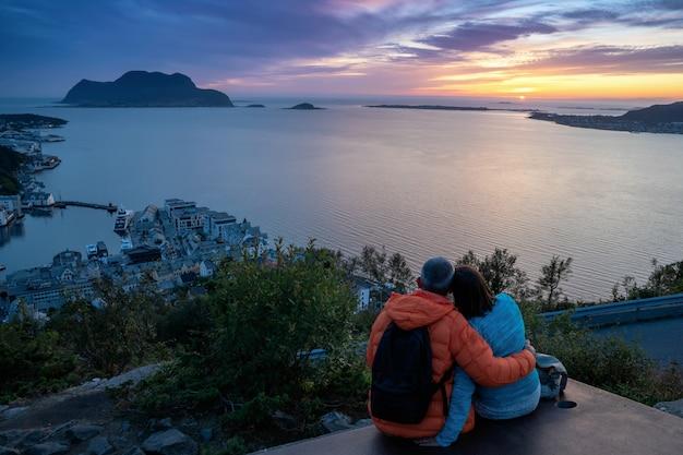Die älteren paare, die auf der bank betrachtet das stadtbild sonnenuntergang, alesund, more og romsdal, norwegen sitzen.