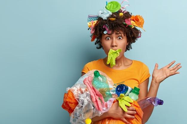 Die ängstliche, frustrierte afroamerikanische frau ist mit plastik überladen, hat den mund mit einem gummihandschuh festgeklemmt, hat augen herausgesprungen, ist besorgt über die naturverschmutzung, hilft bei der reinigung der umwelt und bietet platz für text