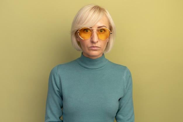 Die ängstliche hübsche blonde slawische frau in der sonnenbrille betrachtet die kamera auf olivgrün
