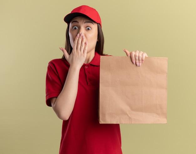 Die ängstliche hübsche lieferfrau in uniform legt die hand auf den mund und hält die papierverpackung auf olivgrün