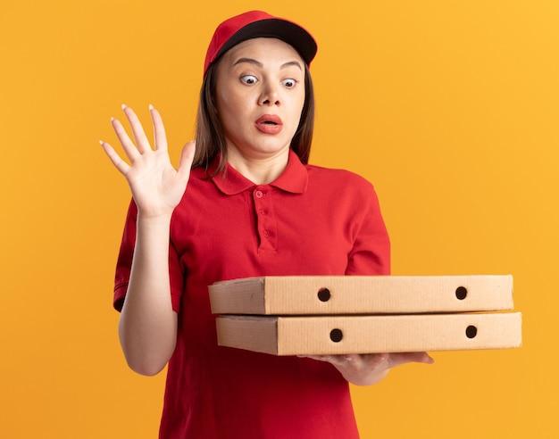 Die ängstliche hübsche lieferfrau in uniform steht mit erhobener hand und hält pizzaschachteln auf orange