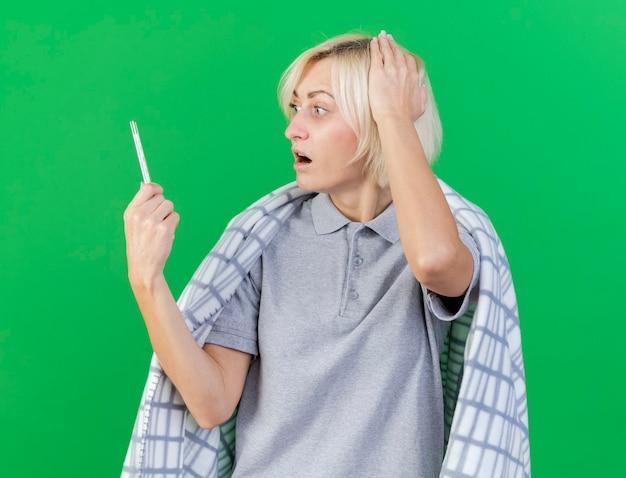 Die ängstliche junge blonde kranke slawische frau, die in karierte griffe eingewickelt ist, schaut auf die hand, die das thermometer setzt