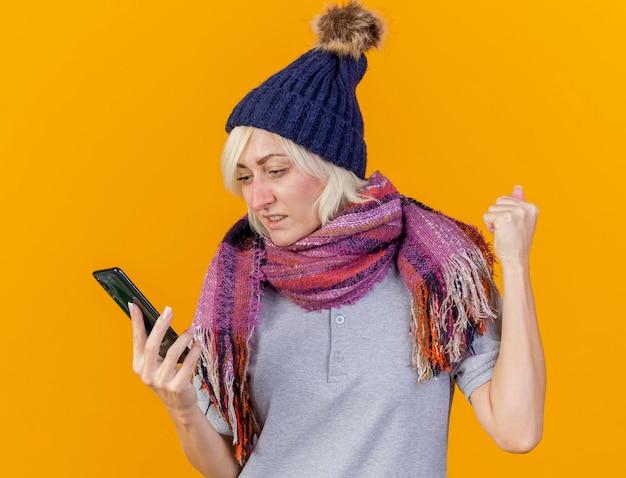 Die ängstliche junge blonde kranke slawische frau, die wintermütze und schal trägt, hält faust hoch