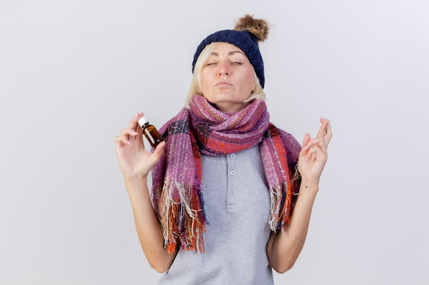 Die ängstliche junge blonde kranke slawische frau, die wintermütze und schal trägt, kreuzt finger und hält medizin in der glasflasche lokalisiert auf weißer wand mit kopienraum