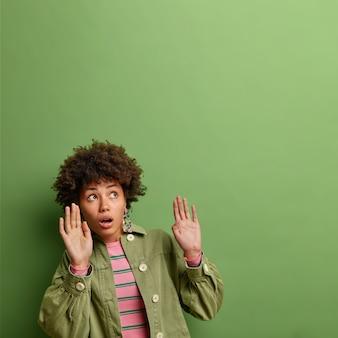 Die ängstliche, schöne afroamerikanerin mit den lockigen haaren hält ihre arme hoch wie etwas, das in stilvollen outfit-posen vor einer leuchtend grünen wand über sie fällt