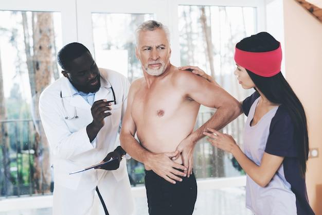 Die ärzte untersuchen einen älteren mann, der rückenschmerzen im rücken hat.