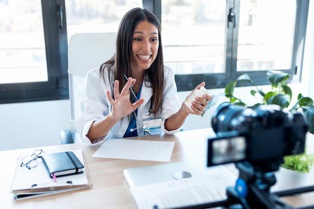 Die ärztin begrüßt die öffentlichkeit, während sie aus der sprechstunde einen videoblog über ihre klinikarbeit macht.