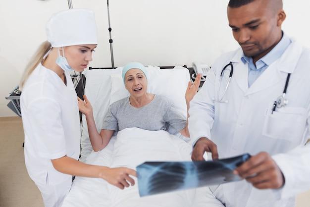 Die ärztin hält ihre röntgenaufnahme im krankenzimmer.