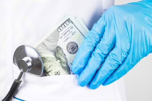 Die ärztin nahm geld. das korruptionskonzept. doktorhand mit geld doktorhand, die geld in seine tasche steckt
