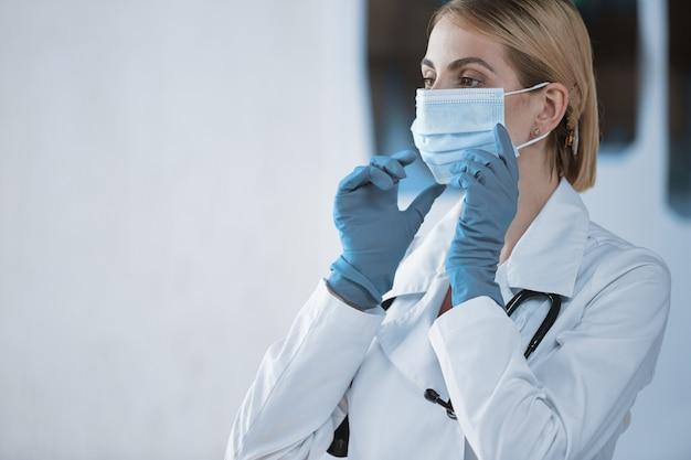 Die ärztin setzt eine medizinische schutzmaske auf