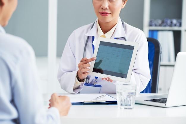 Die ärztin zeigt dem patienten einen kalender mit ihrem zeitplan und bittet darum, das datum für den zweiten termin zu wählen