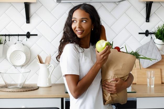 Die afrikanerin, die auf der küche steht, hält eine papiertüte mit lebensmittel und isst einen apfel