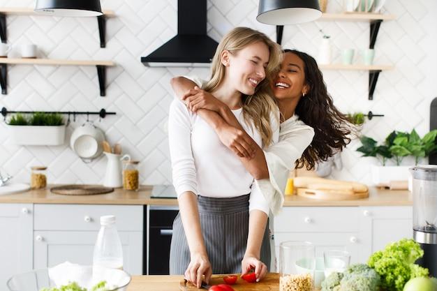 Die afrikanerin, die europäische frau umarmt, stehen sie in der küche und lachen