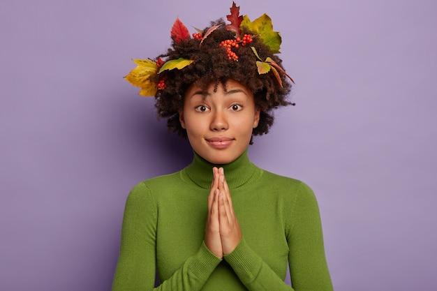 Die afroamerikanische frau hält die handflächen zusammen, betet aufrichtig, hat herbstlaub im haar und trägt einen grünen pullover