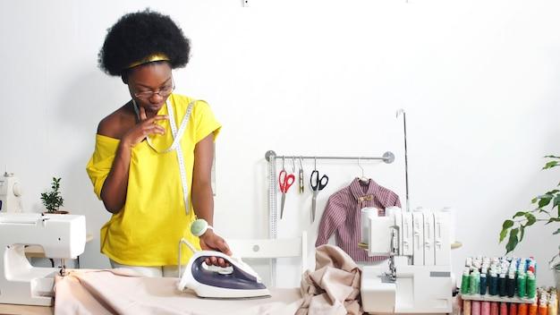Die afroamerikanische näherin glättet den stoff mit einem bügeleisen an ihrem arbeitsplatz, dem arbeitsplatz der näherin in der werkstatt.