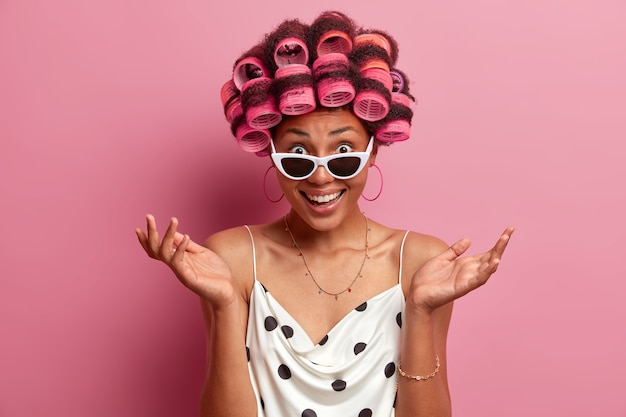 Die ahnungslose fröhliche frau breitet die handflächen aus, hat zweifel, als sie einen unerwarteten vorschlag erhält, ist gut gelaunt, trägt lockenwickler, bereitet sich auf besondere anlässe im leben vor, trägt kleid und sonnenbrille, isoliert auf rosa
