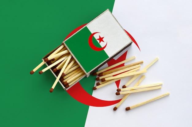 Die algerische flagge ist auf einer offenen streichholzschachtel abgebildet, von der mehrere streichhölzer fallen und auf einer großen flagge liegen