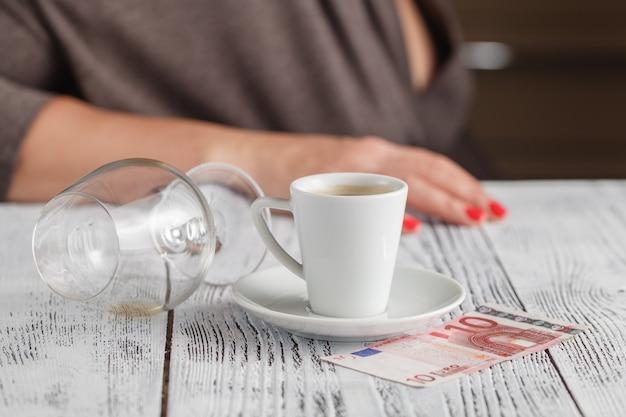 Die alkoholismuskrankheit, die leeres whiskyglas mit frau zeigt, überreicht das gesicht, das über dem glas niedergedrückt wird