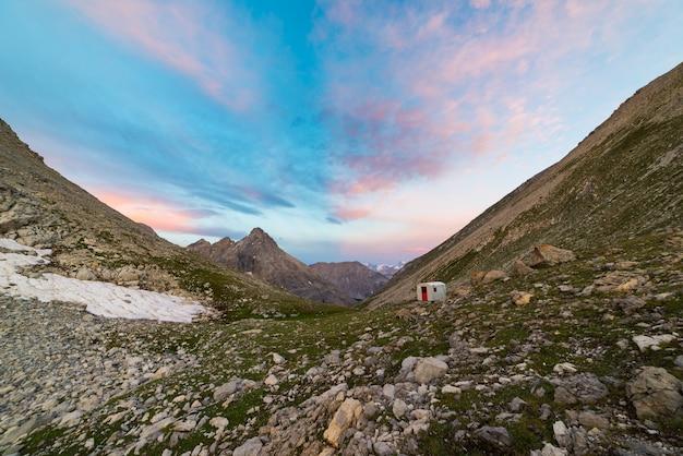 Die alpen bei sonnenaufgang. majestätische spitzen des bunten himmels, drastische täler, felsige berge. weitblick von oben.