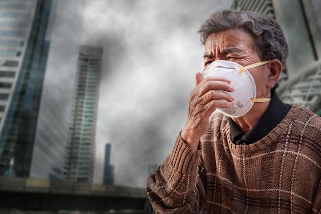 Die alte frau, die eine schablone trägt, fürchten problemluftverschmutzung in der stadt