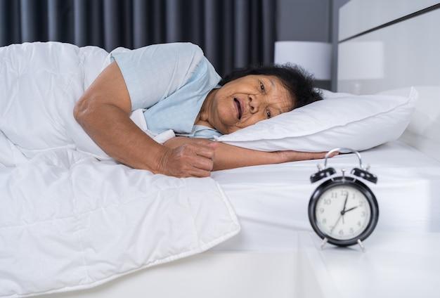 Die alte frau, die unter schlaflosigkeit leidet, versucht, im bett zu schlafen