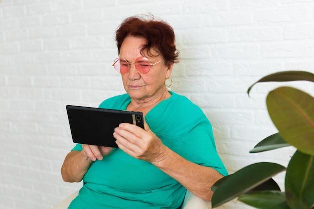 Die alte frau lernt, mit dem tablet über den tablet-computer zu interagieren