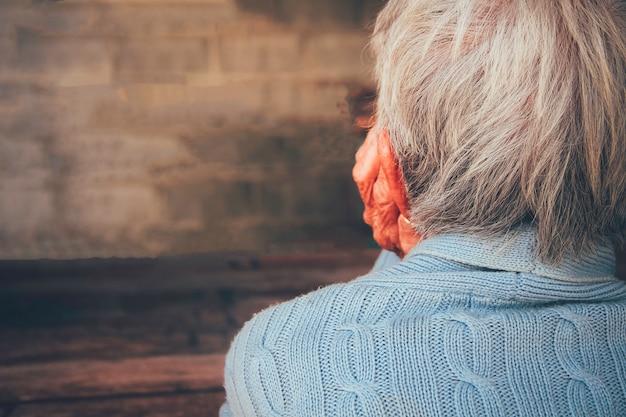 Die alte person war traurig und gestresst. er saß mit einer handstütze auf dem kinn in der dunkelkammer. konzept: demenz, dramatische einsamkeit, traurigkeit, depression, enttäuschung, missbrauch, gesundheit und schmerz.