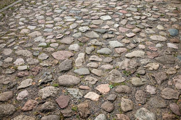 Die alte straße besteht aus steinen und kopfsteinpflaster, auf der straße wächst viel gras