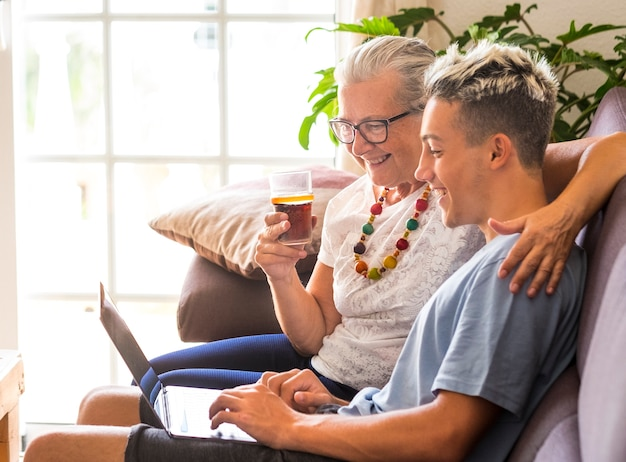 Die alte und die neue generation von millennials teilen sich den gleichen laptop und haben dabei spaß. enkel bringt großmutter das surfen im internet bei. teenager und senioren lächeln glücklich, konzept der liebe und freundschaft