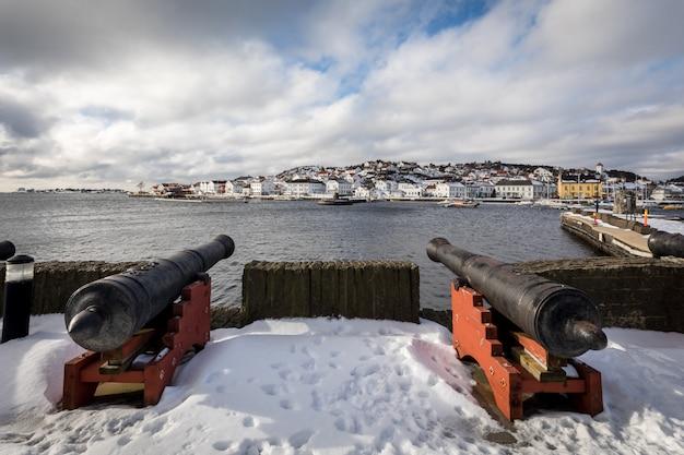 Die alten kanonen in risor, der stadt und dem hafen gesehen