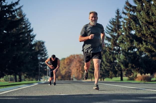 Die alten und jungen sportler beim joggen auf der straße