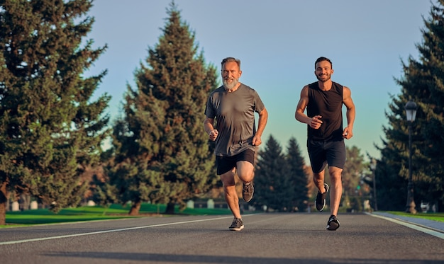 Die alten und jungen sportler, die auf der straße laufen