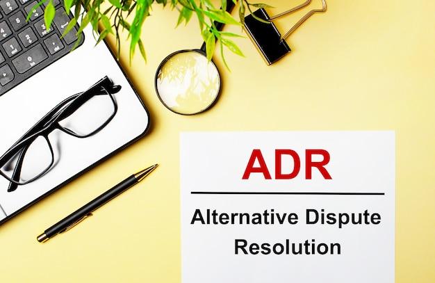 Die alternative streitbeilegung von adr ist rot auf ein weißes blatt papier auf einer hellgelben oberfläche neben einem laptop, einem stift, einer lupe, einer brille und einer grünen pflanze geschrieben