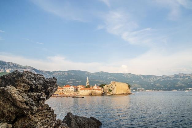 Die altstadt von budva, montenegro hinter dem felsen. schöner blauer himmel mit wolken über den dächern der stadt an der adria