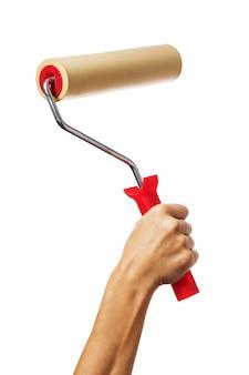 Die angehobene weibliche hand hält eine walze, um den tapetenarbeiter mit dem isolierten werkzeug auszurichten