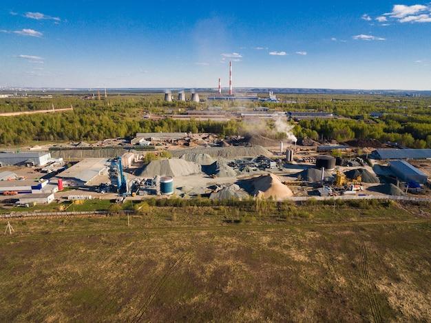 Die anlage liegt inmitten von wäldern und feldern, dahinter befinden sich mehrere fabriken und ein kraftwerk. die anlage dient dem straßenbau