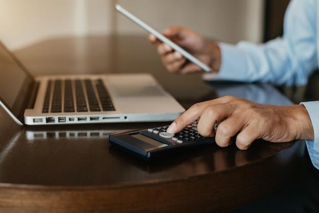 Die anleger kalkulieren mit den investitionskosten des rechners und halten das tablet in der hand.