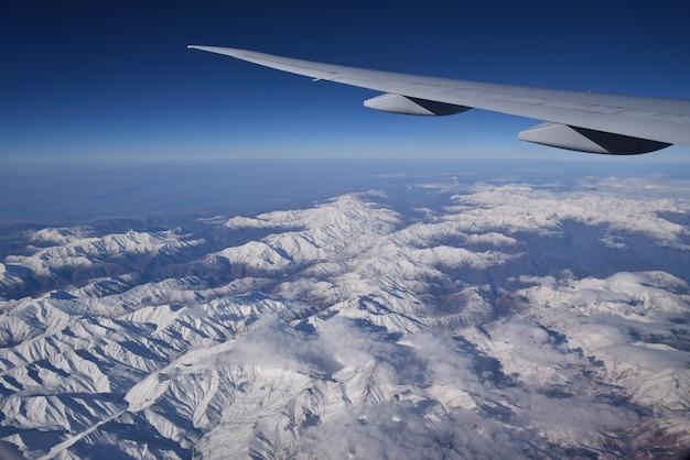 Die ansicht vom flugzeugfenster, schneebedeckte berge zeigend.
