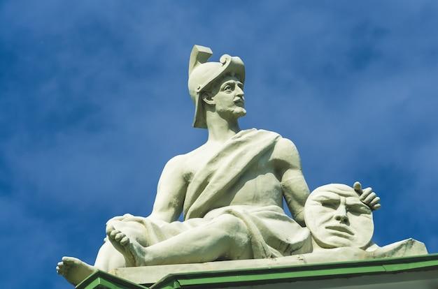 Die antike kriegerskulptur sitzt und hält in den händen eine kreisscheibe mit einem gesicht, einem smiley.