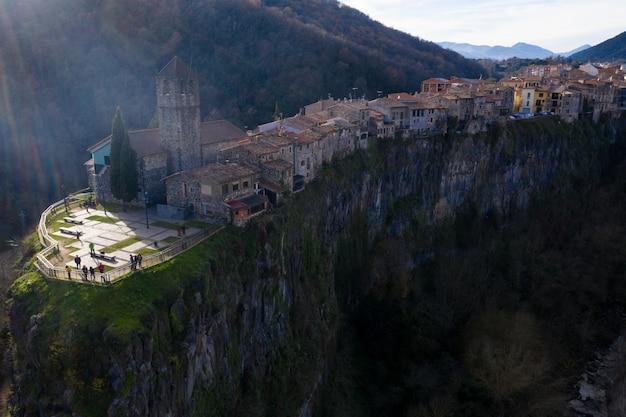 Die antike stadt auf der klippe. luftaufnahmen von einer drohne. schöner sonnenuntergang mit strahlen.