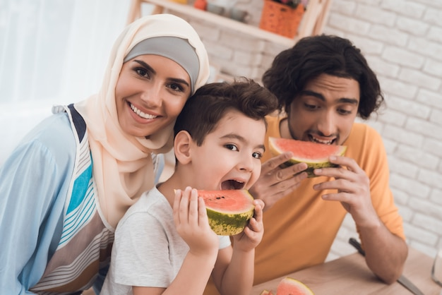 Die arabische familie isst eine wassermelone in ihrer küche.
