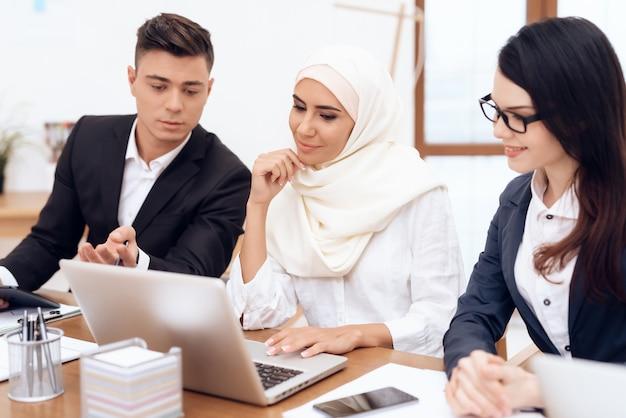 Die arabische frau im hijab arbeitet im büro