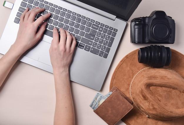Die arbeit des fotografen, fotoretusche. fotoausrüstung, hut, brieftasche, weibliche hände, die auf laptoptastatur auf pastellhintergrund tippen, draufsicht, konzept der freiberuflichen tätigkeit, flache lage