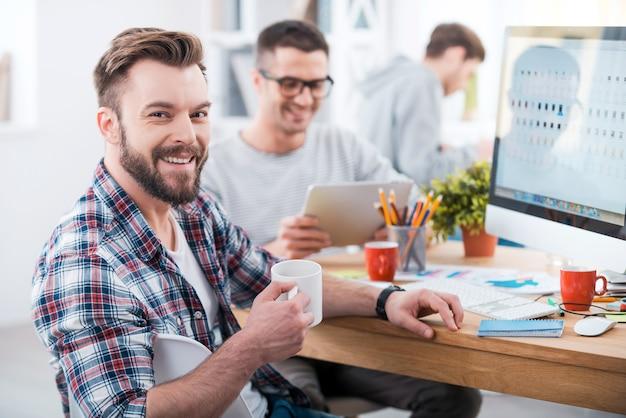 Die arbeit fertigstellen. hübscher junger mann, der eine tasse kaffee hält und lächelt, während er am schreibtisch im büro sitzt, während seine kollegen im hintergrund arbeiten