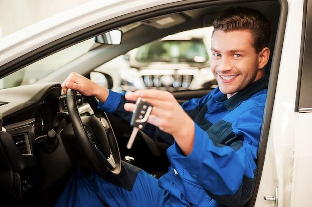 Die arbeit ist erledigt. fröhlicher junger mann in uniform, der die hand mit schlüsseln ausstreckt, während er in einem auto in der werkstatt sitzt sitting