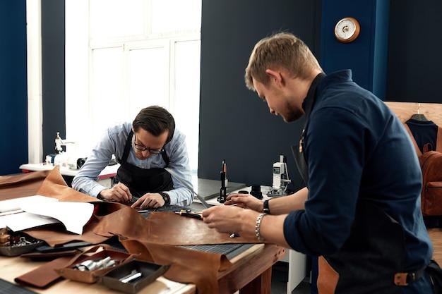 Die arbeit von schneidern in der werkstatt, 2 junge handwerker in der werkstatt zum nähen von ledertaschen während der arbeit, handgefertigte lederwaren, familiärer kleinbetrieb.