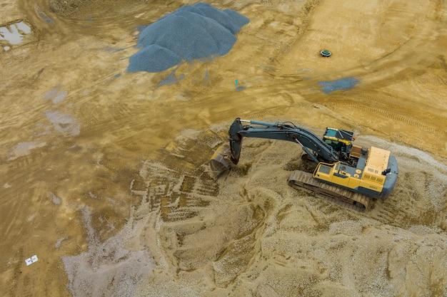 Die arbeiten mit im bau befindlichen baggerausrüstungen bei der herstellung von erdarbeiten arbeiten durch die gebietsverbesserung.