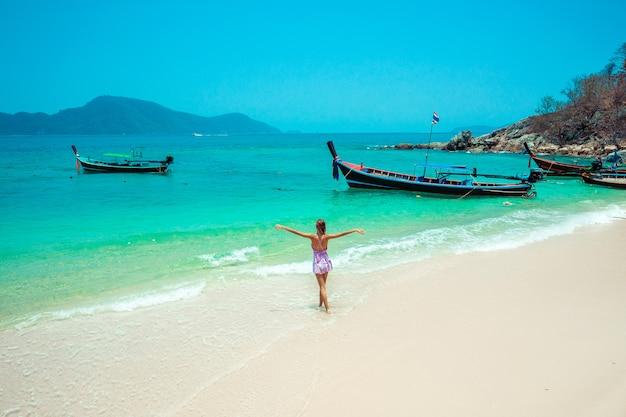 Die arme der glücklichen reisenden frau öffnen sich im entspannenden kleid und schauen mit traditionellen langschwanzbooten auf die schöne naturlandschaft. touristischer meeresstrand thailand, asien, sommerferienurlaubsreise -